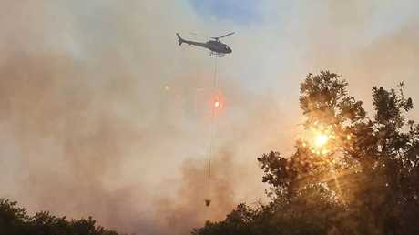 A waterbombing helicopter works to control the blaze. Picture: Woodgate Rural Fire Brigade