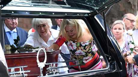 Television personality Kerri-Anne Kennerley places her hand on the casket following the funeral for her husband John Kennerley Picture: AAP Image/Joel Carrett
