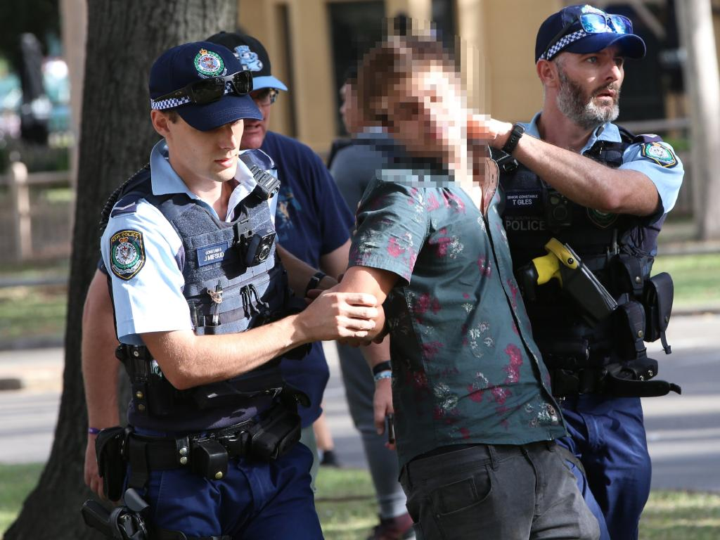 A man as he is detained by police outside the main entrance to the Ultra Australia festival. Picture: Damian Shaw