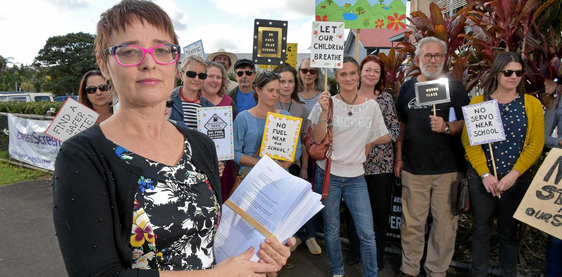 Members of the Maleny community gather to protest the proposed service station opposite the local primary school with event organiser Angie Kelly.