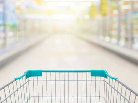 Shopping cart view with milk and yoghurt product shelves aisle in supermarket
