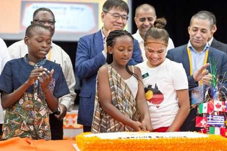 Cutting the cake are (from left) Enock Mukeba, Mary Inkindi and Evie Adams on Harmony Day celebrations at Darling Heights State School, Wednesday, March 14, 2019.