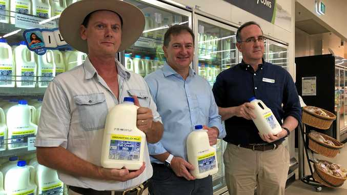 HELPING FARMERS: Dairy farmer and Fraser Coast councillor James Hansen with member for Wide Bay Llew O'Brien and Woolworths' director of fresh food Paul Harker with the milk that is no longer $1 a litre.