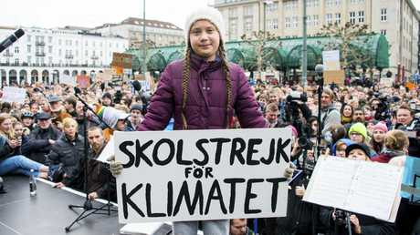 Swedish climate activist Greta Thunberg holds a slogan that translates to 'School Strike For The Climate' at a protest rally in Hamburg, Germany on March 1. Picture: Daniel Reinhardt/AP