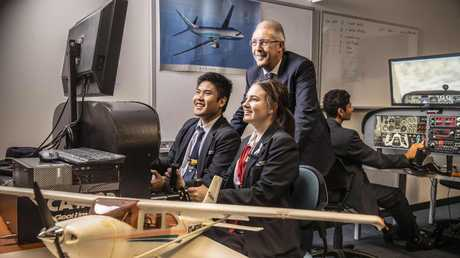 Students Matthew Saengrat and Grace Alberti from Brisbane's Aviation High practice flying on simulators while principal David Munn watches on. Photo: Glenn Hunt / The Australian