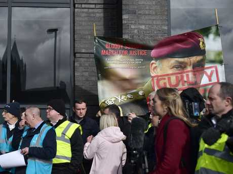 Families of those killed during Bloody Sunday march through Bogside with a banner featuring the image of a former soldier in Londonderry, Northern Ireland. Picture: Getty Images
