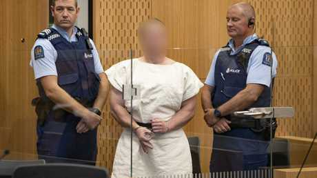 Brenton Tarrant, charged with murder, makes a hand gesture associated with white supremacy during his appearance in the Christchurch District Court. Picture: AAP/New Zealand Herald Pool/Mark Mitchell