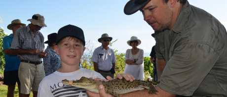 Spencer Riys pats a baby saltwater crocodile at the memorial for Bismarck. Pic: ELISABETH CHAMPION