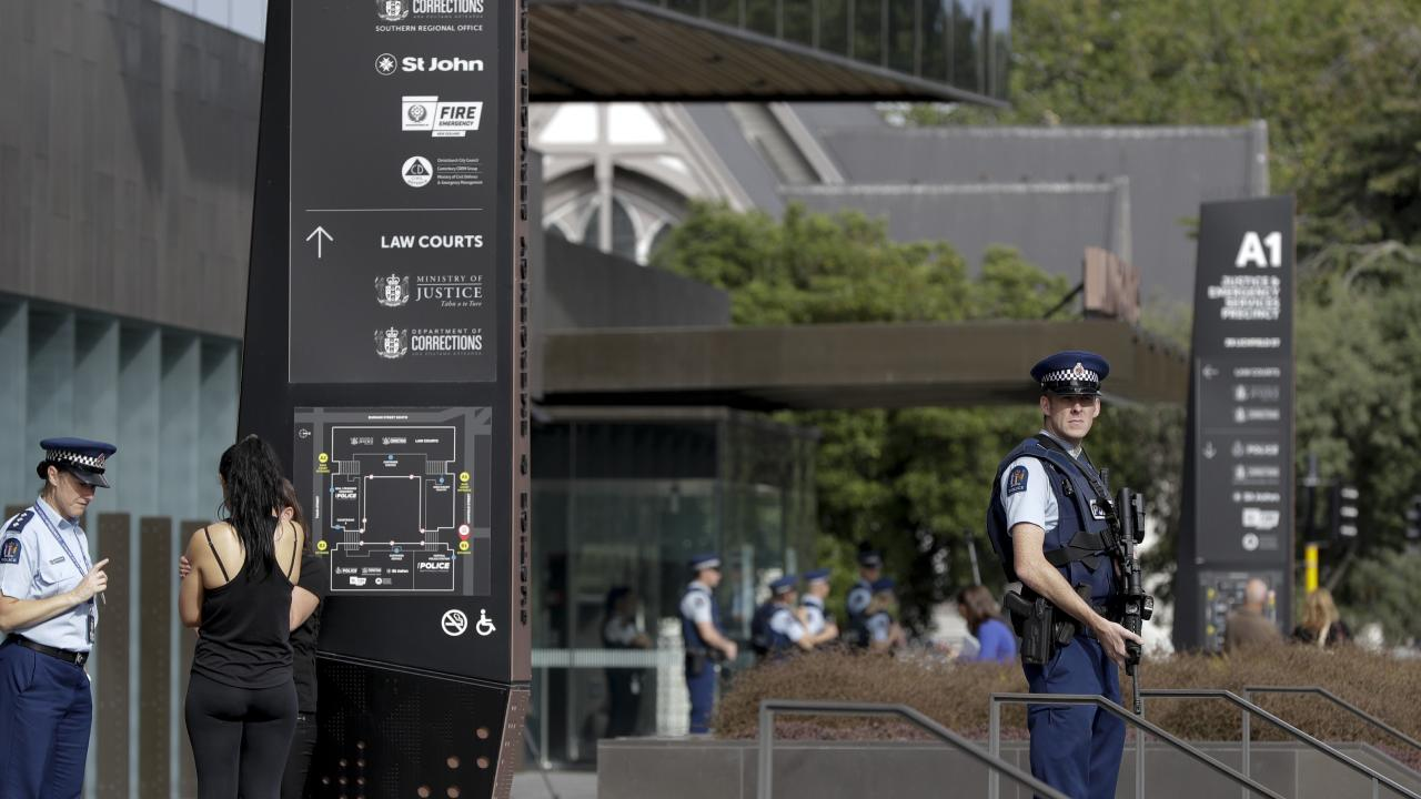 Police stand guard outside the district court building in Christchurch. Picture: AP Photo/Mark Baker