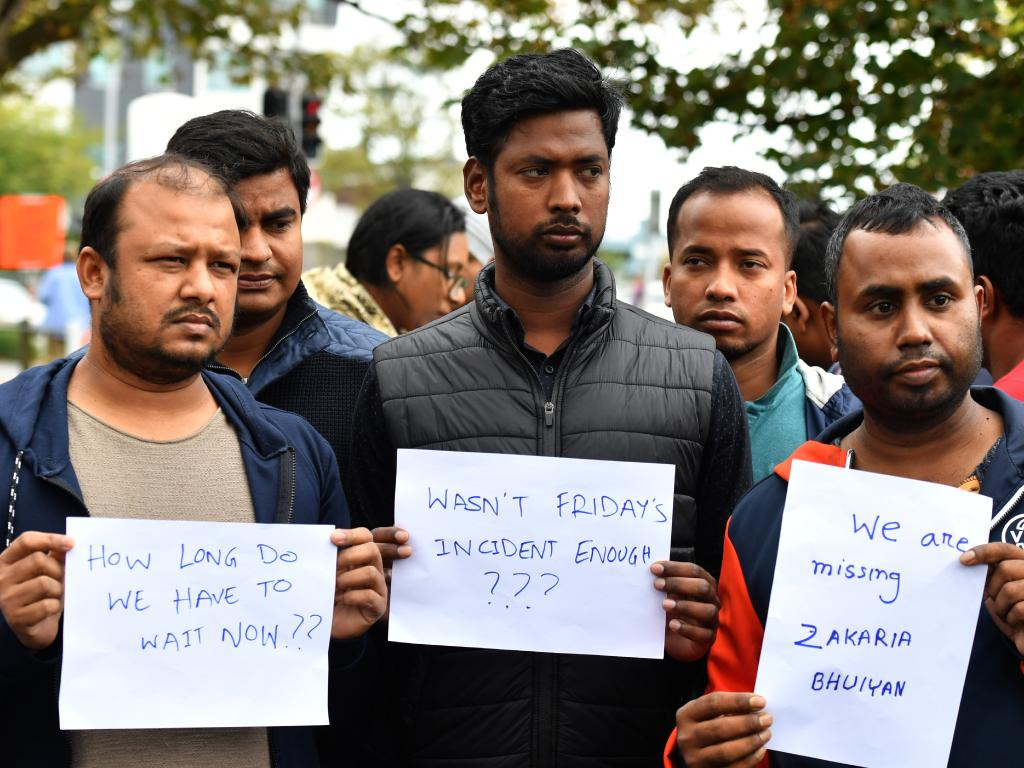 Friends of a missing man Zakaria Bhuiyan hold up signs of him outside a refuge centre in Christchurch. Picture: AAP