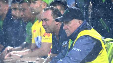 Coach Ricky Stuart watches on in the rain.