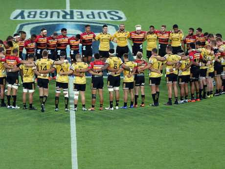 The Chiefs and Hurricanes come together for a moments silence before the start of their Super Rugby match. Picture: Getty Images