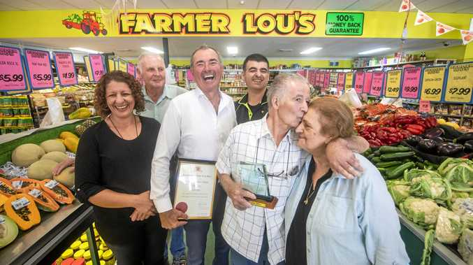 Lou Felice gives his wife Lucy a kiss after he was awadred a NSW Government Community Service Award as daughter Tina Felice, family friend Phil McCure, Chris Gulaptis and son Paul Felice look on.
