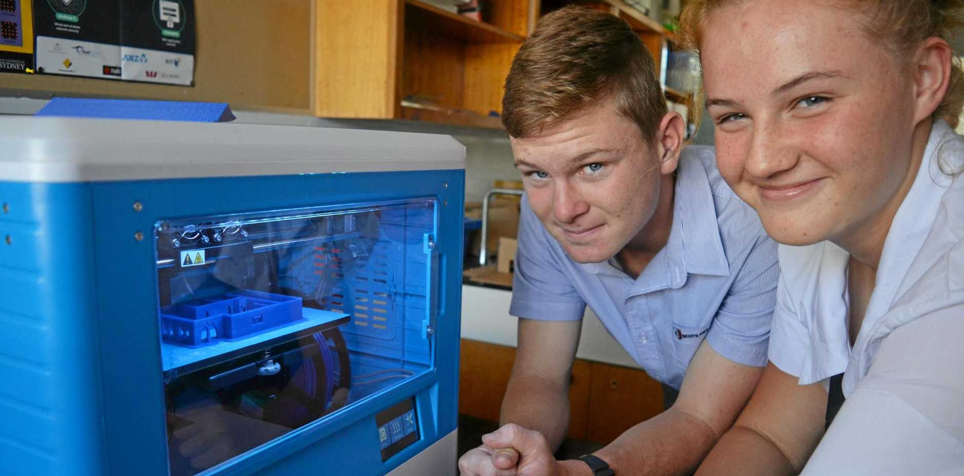 TEACHING TECH: Scots PGC students Alex Elsing and Chloe Paganin are building model homes with a 3D printer in their STEM class.