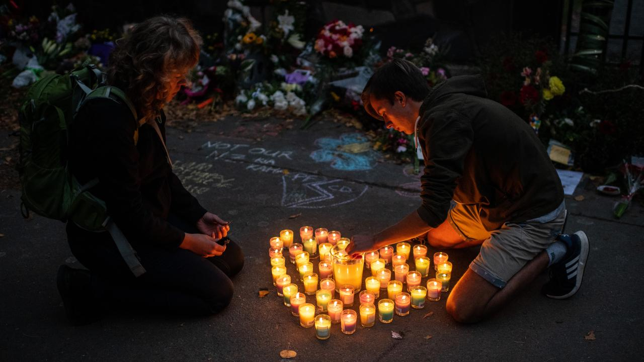 People light candles next to flowers and tributes laid in Christchurch. Picture: Carl Court/Getty Images