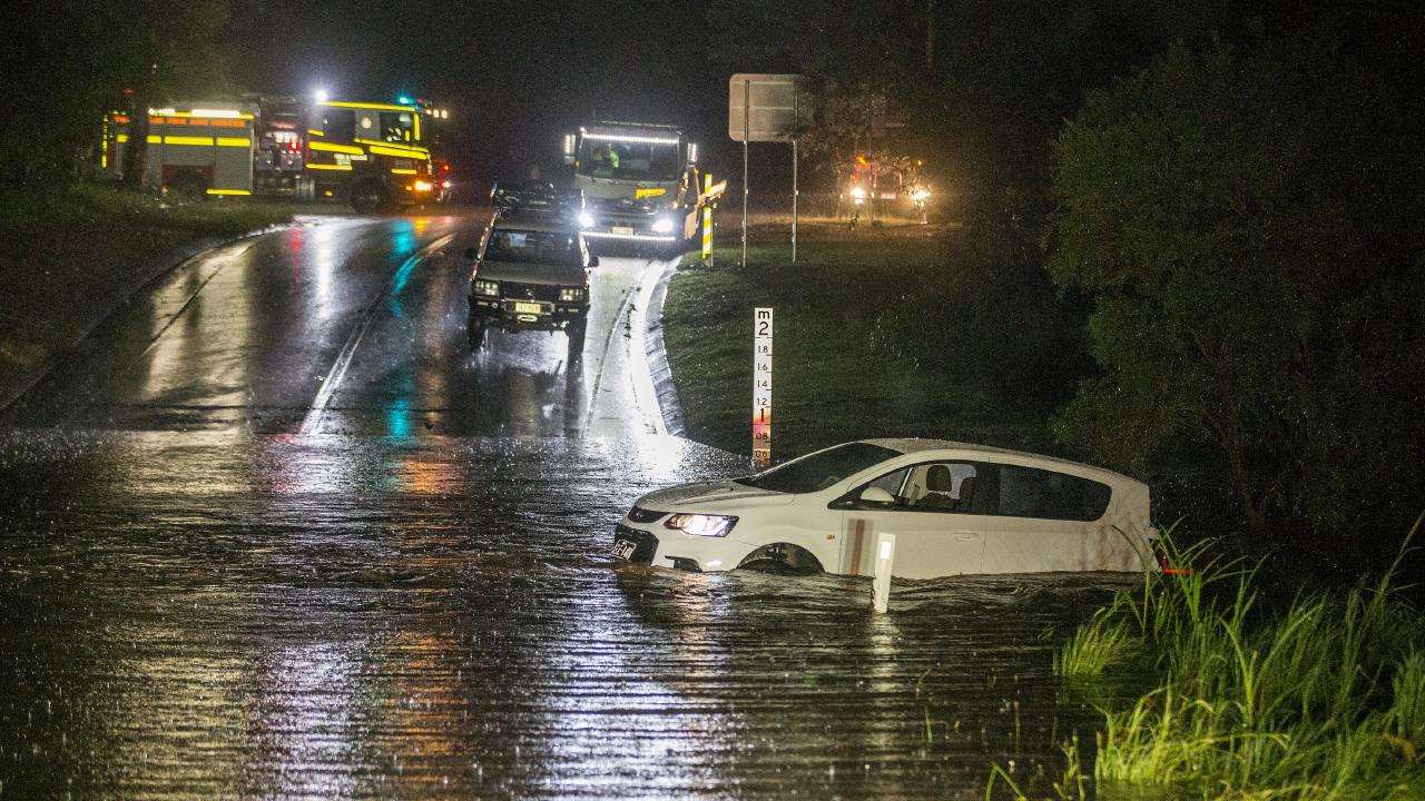 A vehicle is stranded on a bridge in the water along Hardys Rd, Bonogin on Friday night. Picture: Jerad Williams