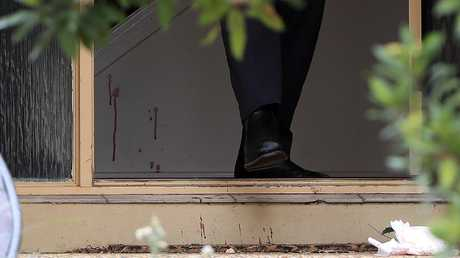 Blood stains near the entrance as police comb the scene at Kumnick Street, Upper Coomera after a shooting. Pics Adam Head