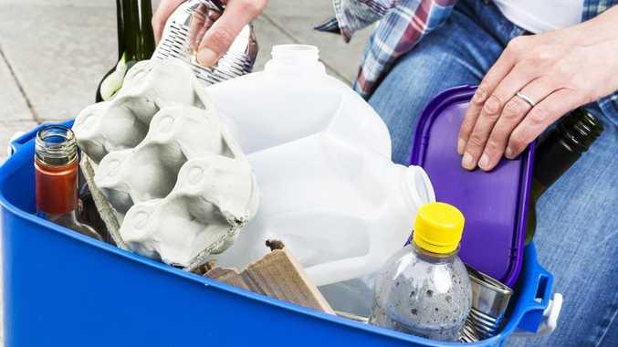 Woman filling a blue recycling bin the wrong way.
