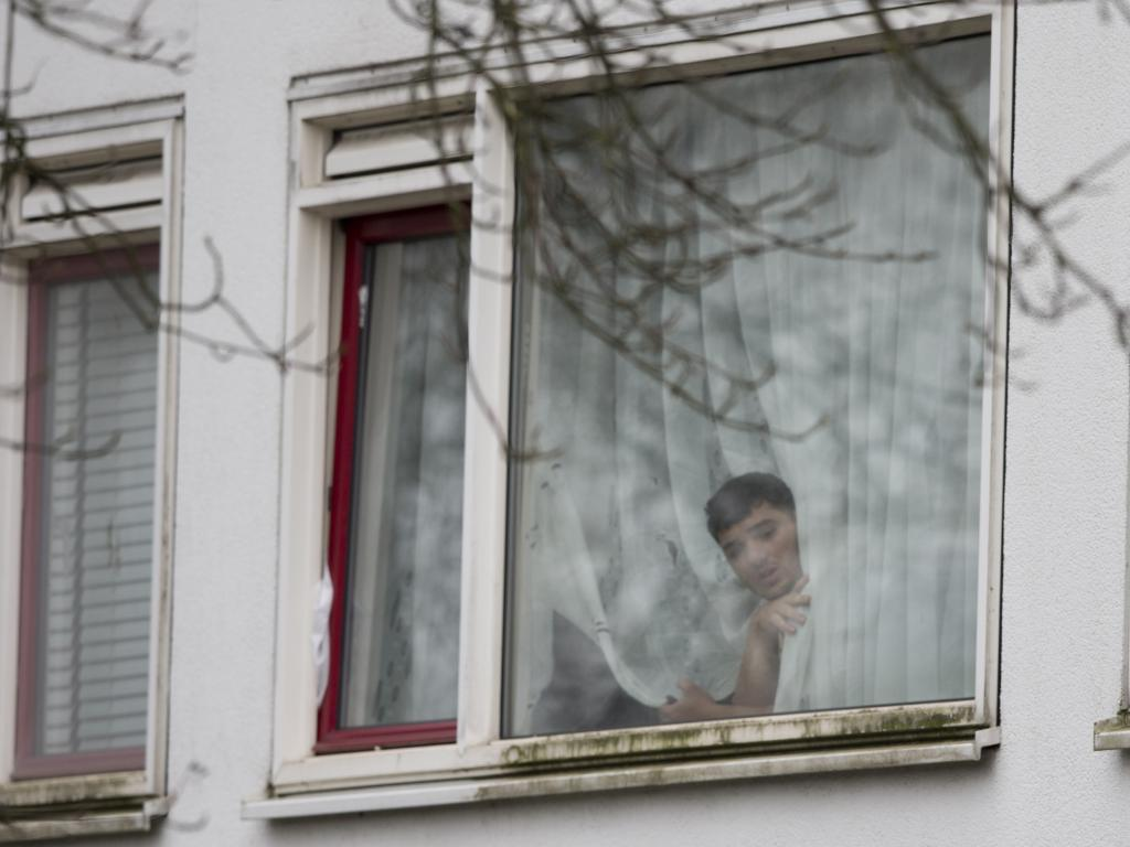 A resident peers from a window as Dutch counter terrorism police prepare to enter a house after a shooting in Utrecht, Netherlands. The gunman has been caught. Picture: AP Photo