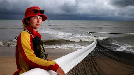 Holloways Beach lifeguard Lucy Chapman checks the nets as surf pounds the beach front PICTURE: ANNA ROGERS