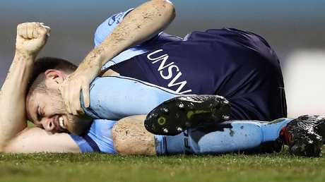 Sydney FC defender Ben Warland clutches his left knee during the match against Melbourne City on Sunday. Picture: Getty Images