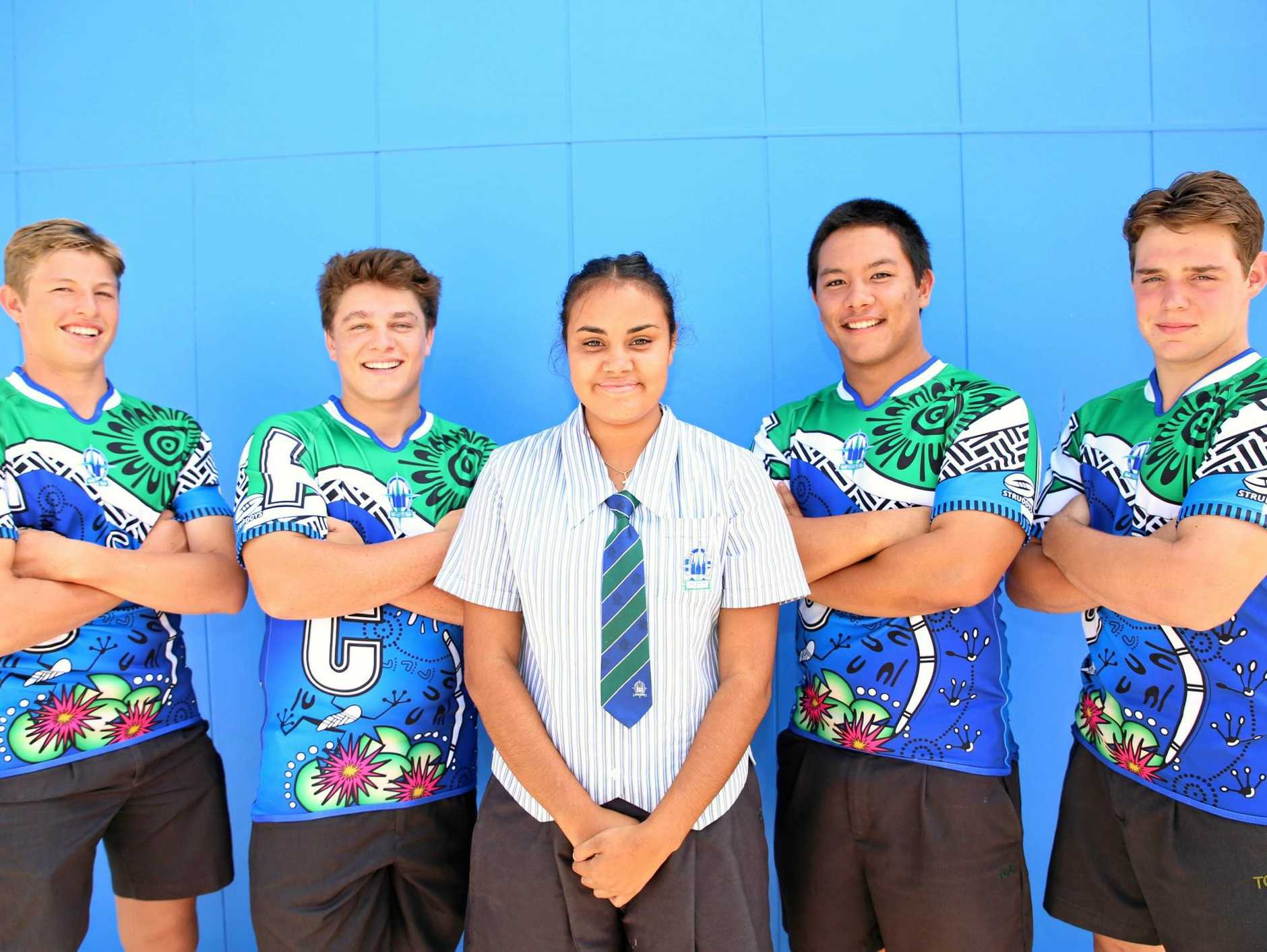 STRIKING: The Cathedral College's Year 10 student and emerging Darumbal artist Seini Tonga who is proud to see her creative design come to life when Open A rugby league players Thallon Peters, Jackson Warde, Riley Boaza and Mitchell Leard-Lamont try the jerseys on for size.