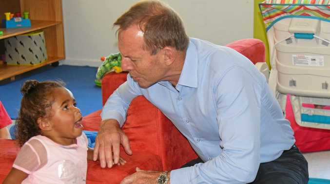 FRIENDLY CHAT: Mr Abbott with one of the Gundoo Childhood Centre children in Cherbourg.