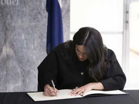 The Duchess of Sussex signs the book of condolence, during a visit to the New Zealand High Commission in London. Picture: AP