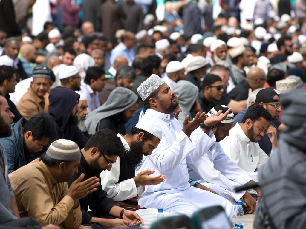 Muslims answer the call to pray at Hagley Park, opposite the Al Noor Mosque. Picture: AAP Image/SNPA, Martin Hunter