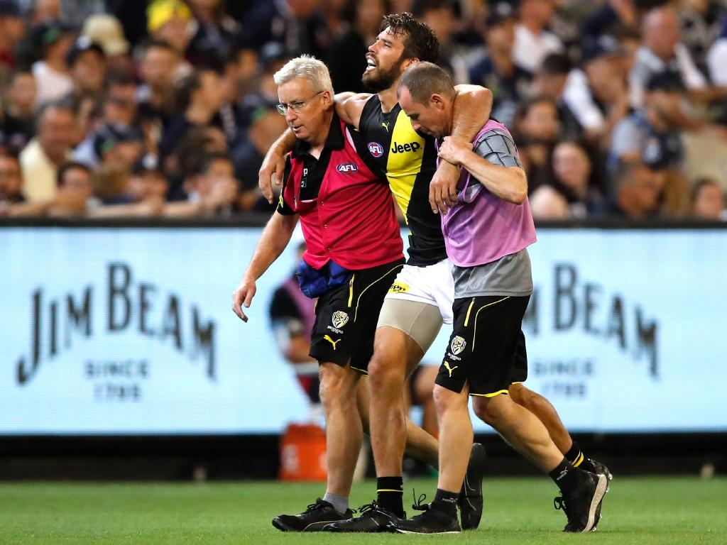 Alex Rance is assisted off the ground by trainers. (Photo by Dylan Burns/AFL Photos/Getty Images)