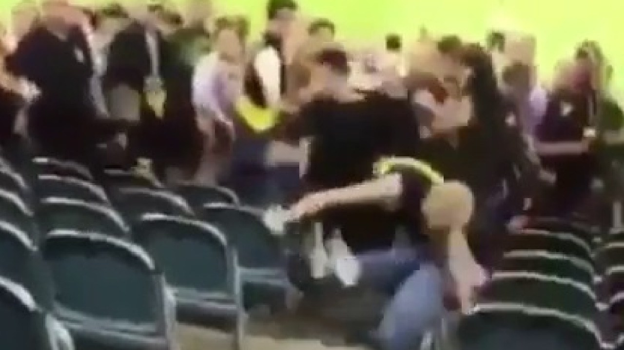 People look on as one man is thrown to the ground and bashed.