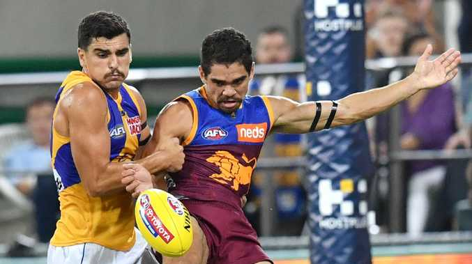 Brisbane's Charlie Cameron prepares to kick a super goal despite the efforts of Tom Cole. Picture: AAP