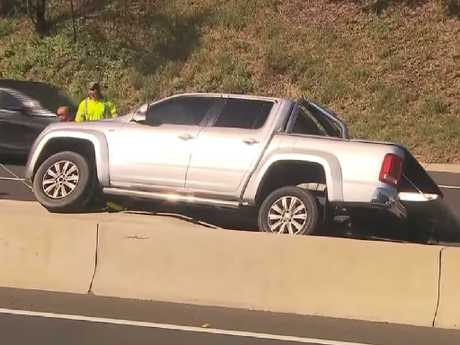A man has been arrested after driving down the wrong side of the M5 and crashing his ute on a concrete dividing barrier. Picture: Channel 7