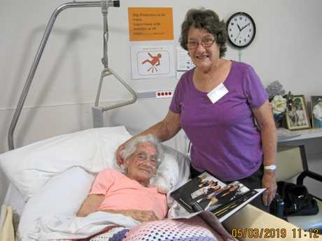 Nancy Pitkin with her 100-year-old mother Ina Smith, who is reading the page in the book that shows Karen Williams, Buddy's daughter, visiting Ina in Highview in September 2018. Ina made Buddy his pair of long trousers back when he came to live in Dorrigo.