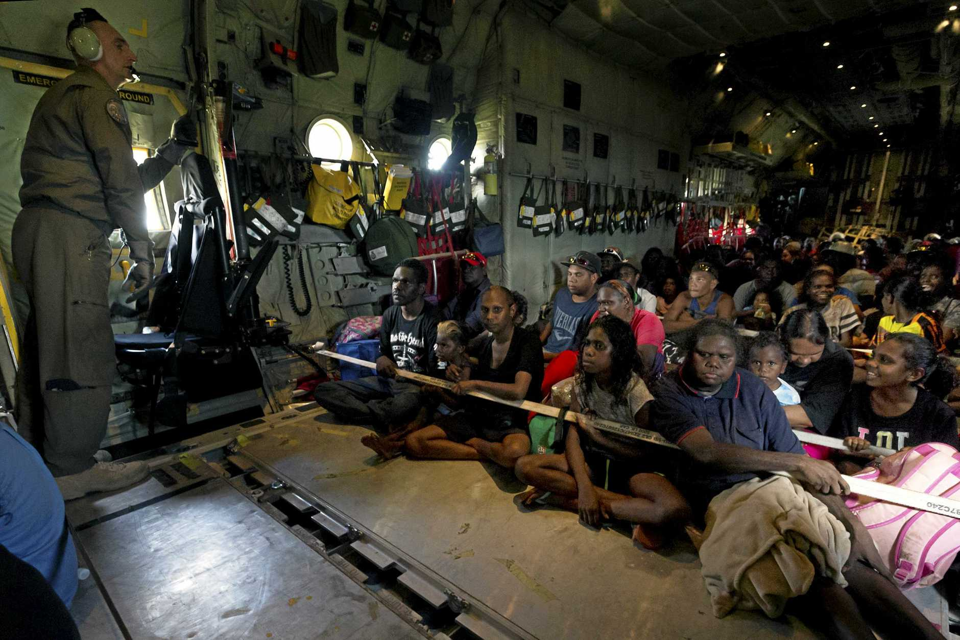 A supplied image obtained Friday, March 22, 2019, of a Royal Australian Air Force loadmaster with locals during an evacuation flight from Groote Eylandt on board a C-130J Hercules as cyclone Trevor approaches. (AAP Image/Supplied by Department of Defence) NO ARCHIVING, EDITORIAL USE ONLY