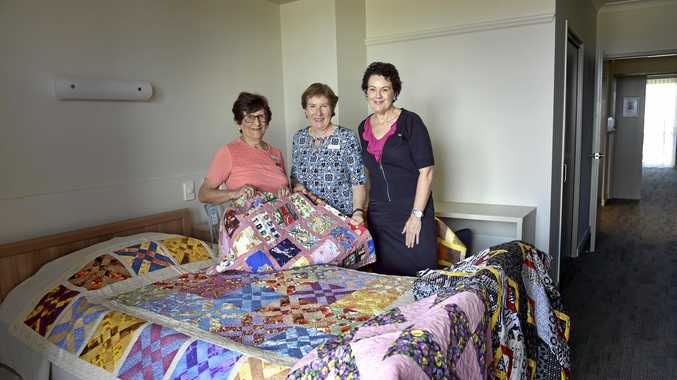 WELCOMING: Placing quilts for the opening of the Ozcare Toowoomba aged-care facility in Greenwattle St are (from left) Toowoomba Quilter Club members Fay Suley and Lee Hicks with facility manager Elizabeth Klein.