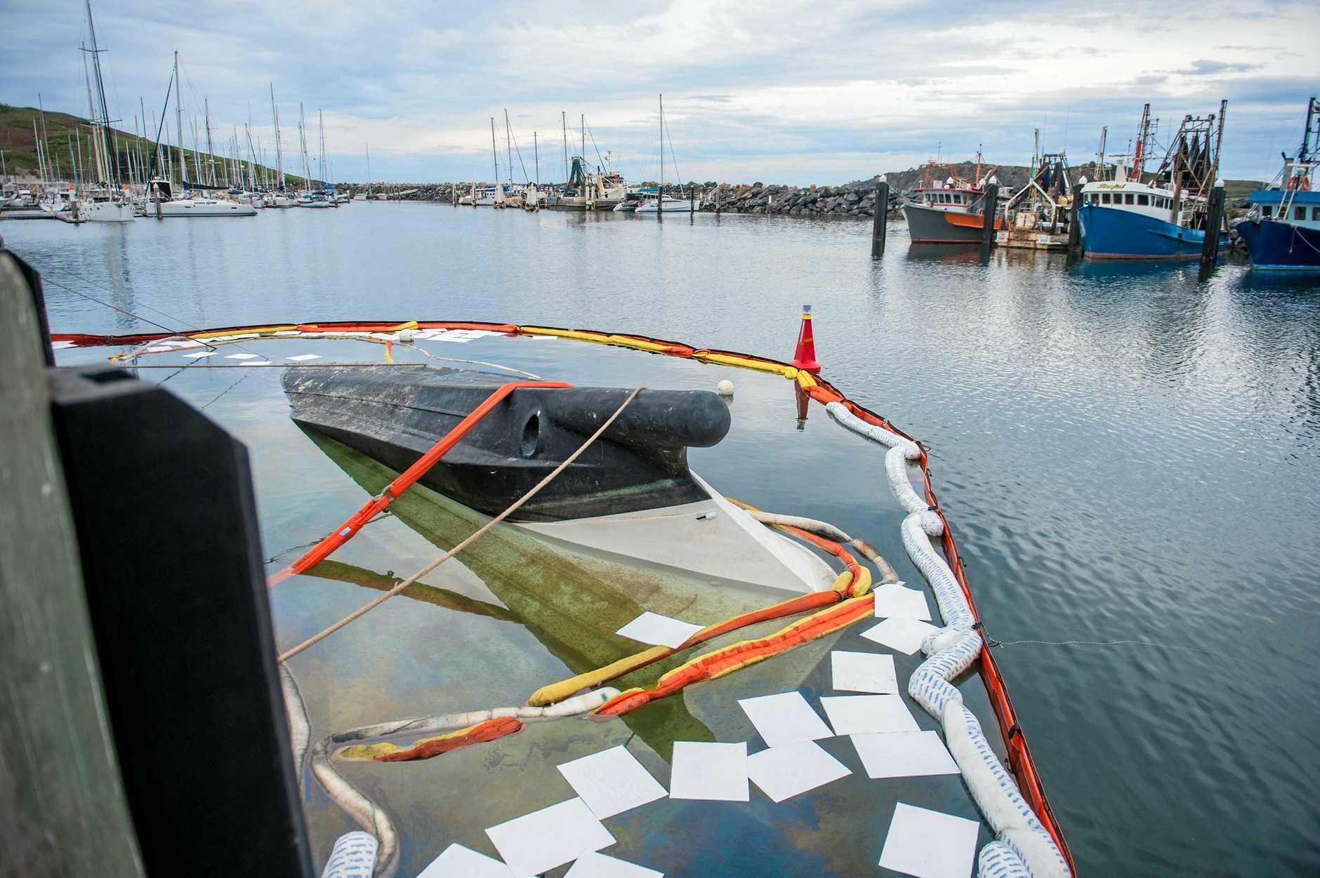 Capsized boat awaits removal in the marina.