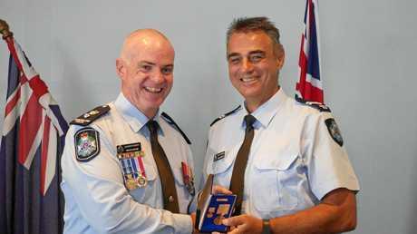 Superintendent Bruce McNab presents Senior Constable Josh Gamosh with his medals.