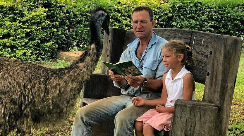 ASSISTANT TEACHER: Fred the emu joins in on reading time with dad Rob McArthur and distance education student daughter Eliza.
