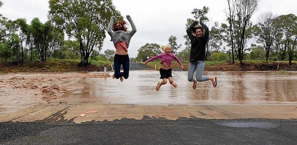 Gabby Rayner (15), Summer Barnett (9), and Marsha (21) an au pair from the Netherlands were over the moon about the 105mm of rain received at Wolfgang, between Clermont and Moranbah. Table Creek flooded, meaning Gabby and Summer couldn't get to school on Thursday, which they were very happy about.