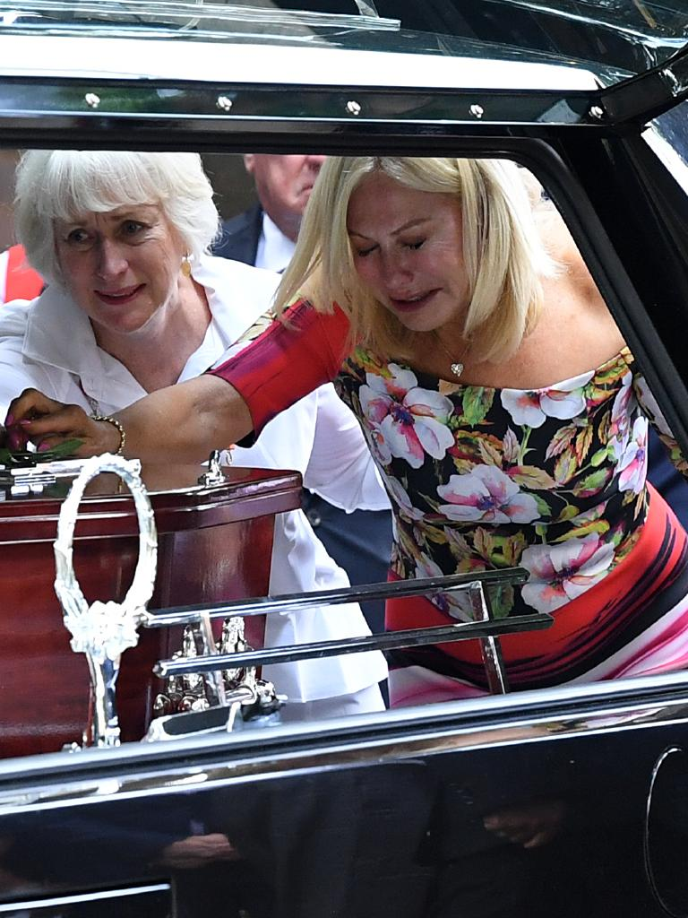 Television personality Kerri-Anne Kennerley places her hand on the casket at the funeral for her husband John Kennerley. Picture: Joel Carrett