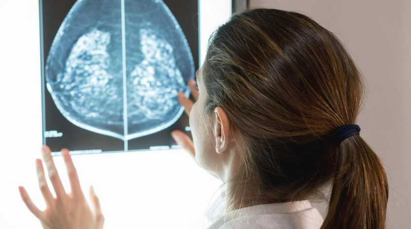 A female gynocologist inspects at a patient's mammogram.