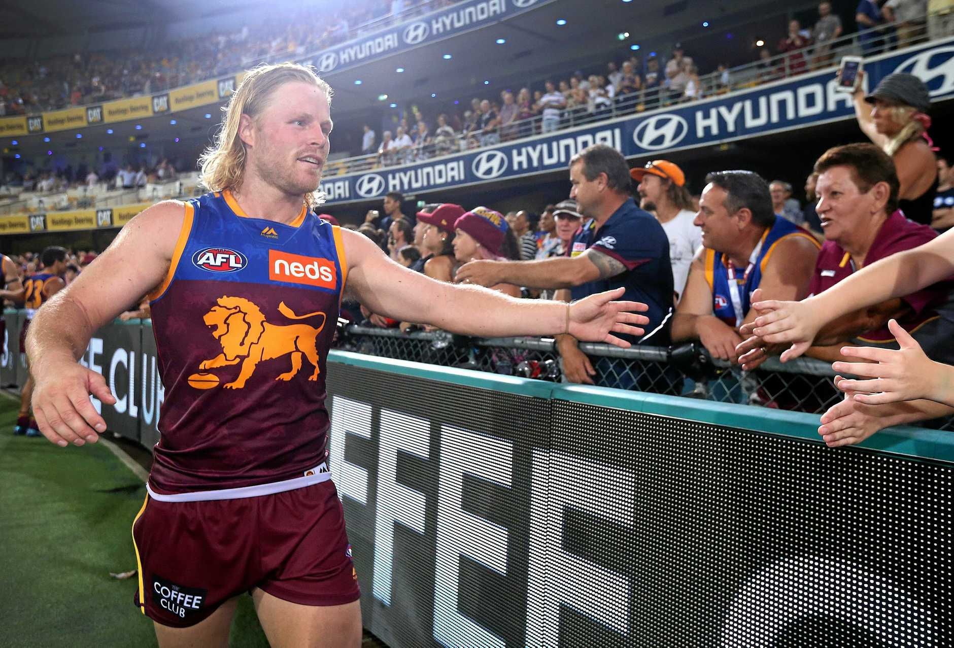 Daniel Rich celebrates with fans after the Lions' opening-round win.