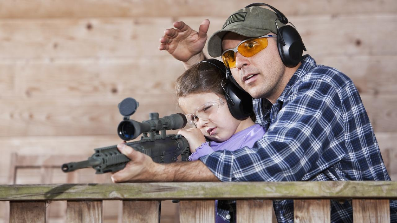 A father teaching his daughter how to shoot a rifle.