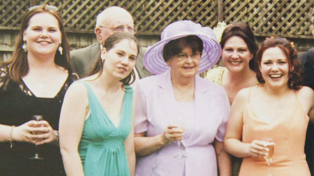 Kirra McLoughlin (in orange) surrounded by family on her wedding day.