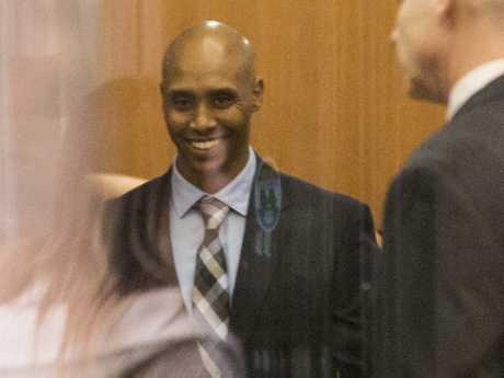Mr Noor arrives at the courthouse smiling beside his lawyers on Friday.