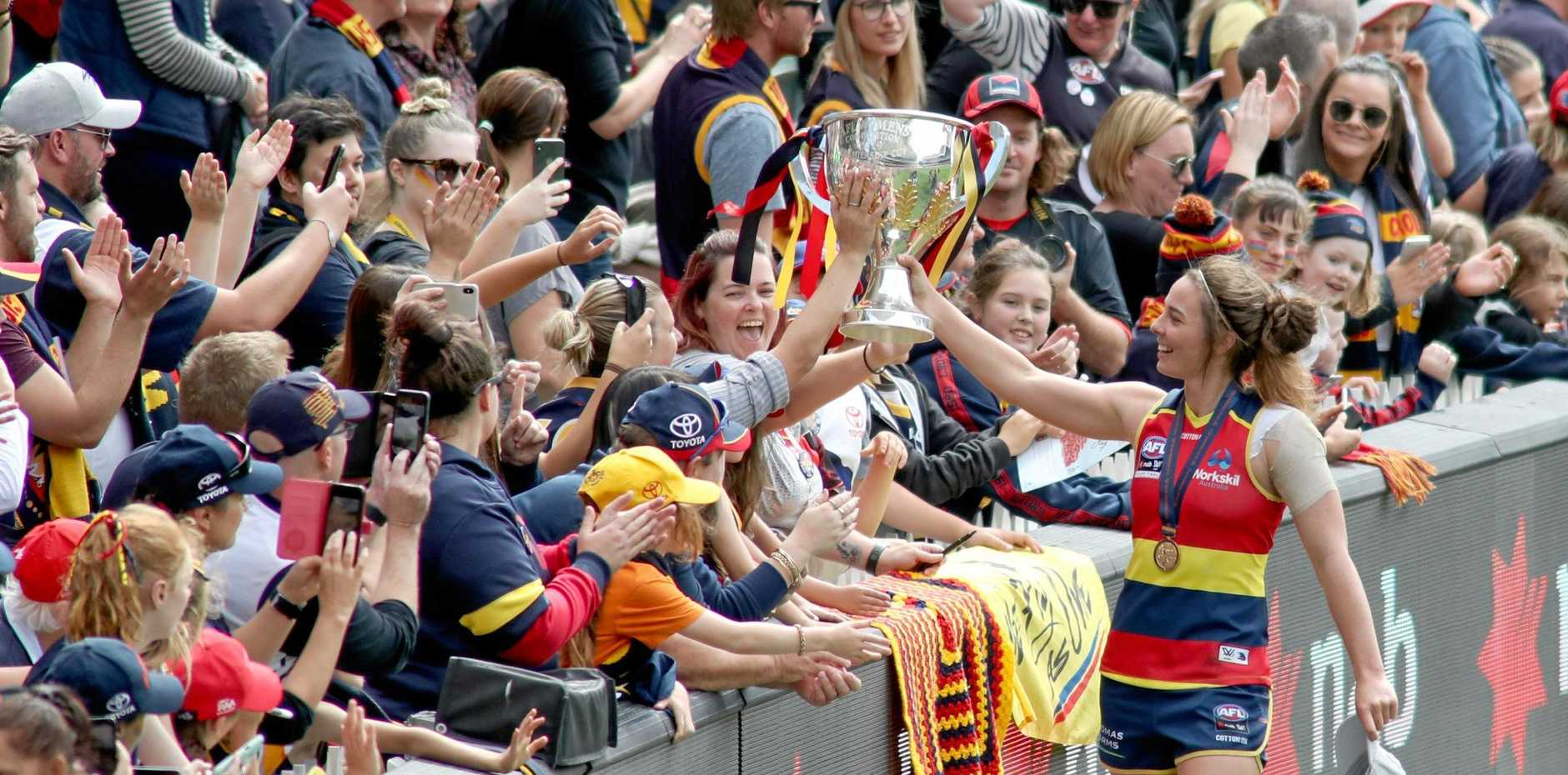 Jenna McCormick of the crows celebrates with fans during the AFLW grand final match between the Adelaide Crows and the Carlton Blues at Adelaide Oval in Adelaide, Sunday, March 31, 2019. (AAP Image/Kelly Barnes) NO ARCHIVING, EDITORIAL USE ONLY
