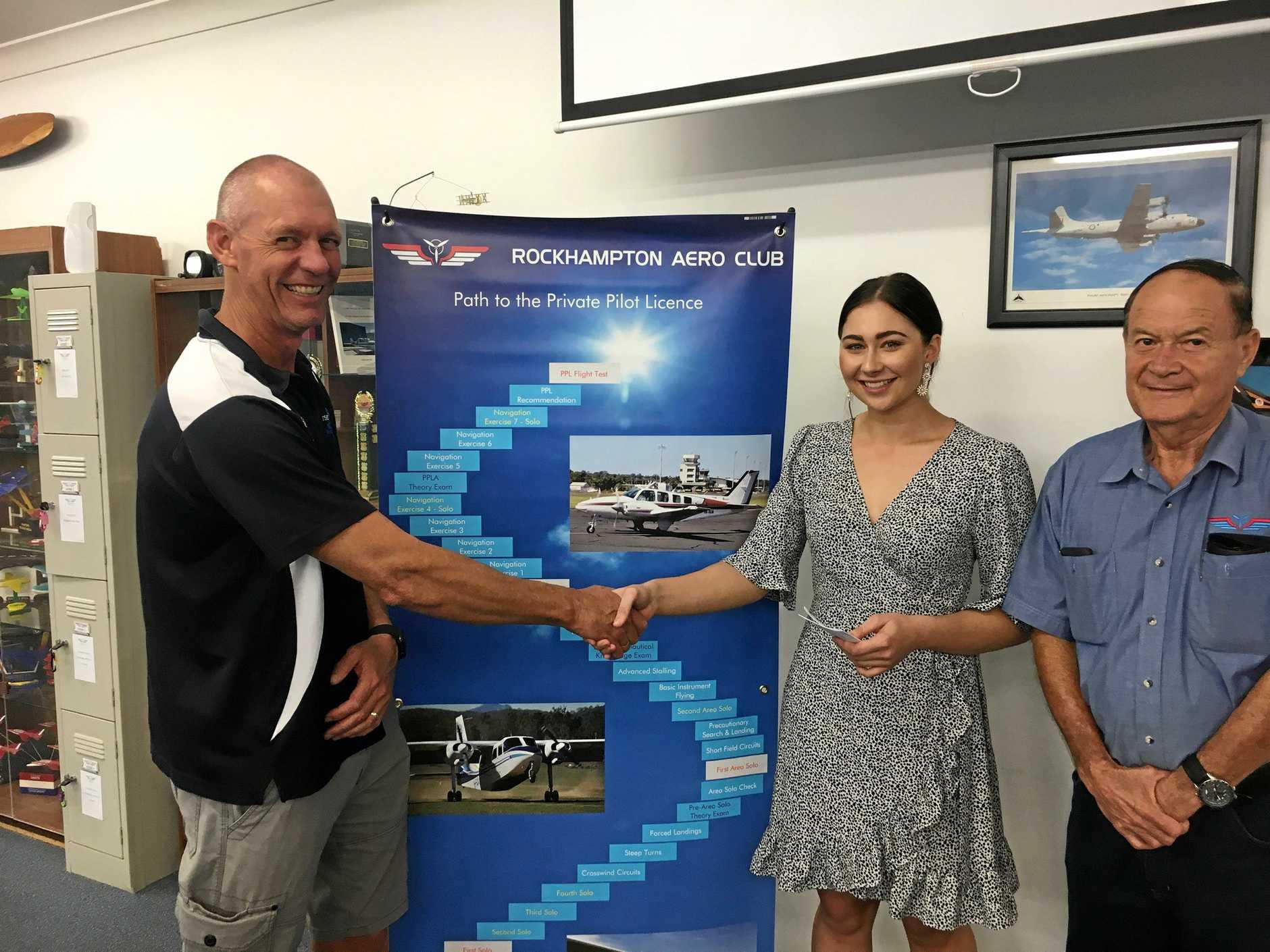 Rob Mitchell from Rockhampton Control Tower/Airservices Australia, Kate Lovegrove and RFACA regional director Graham Dooley at a formal presentation at Rockhampton Aero Club on Friday night.