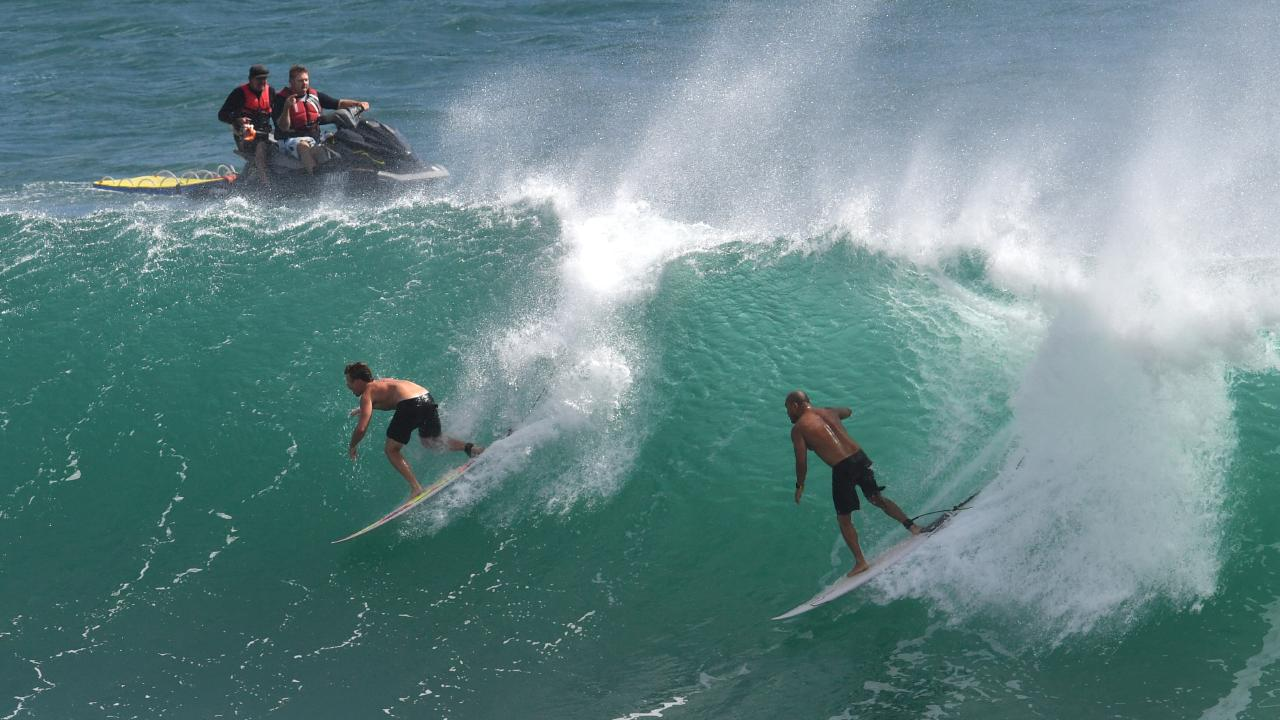 Surfers enjoying some big swell. (AAP Image/Darren England) NO ARCHIVING