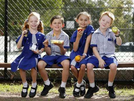 Harper Baer, 6, Fletcher Lee, 7, Ruby Lee, 9 and Oliver Baer, 6, pupils at St Thomas' in  Camp Hill, Brisbane, enjoy  healthy food options from their tuckshop.